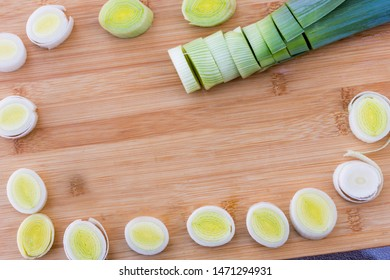 Organic fresh cutted leeks on the wooden cutting board. Leek cut by means rings on a chopping board. Slices of the fresh green leek. Cooking ingredients. Frame. Empty space for text input