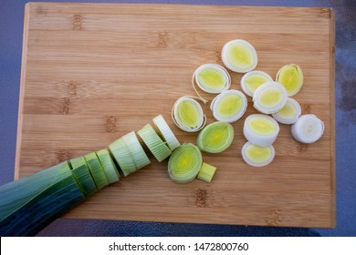 Organic fresh cutted leeks on the wooden cutting board. Leek cut by means rings on a chopping board. Slices of the fresh green leek. Cooking ingredients.