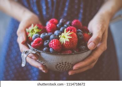 Organic fresh harvested berries. Hands holding fresh juicy berries, closeup.