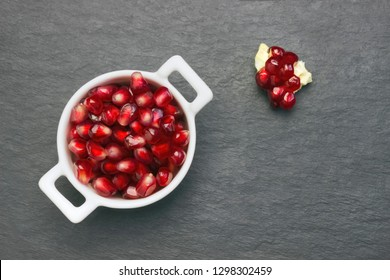 Organic fresh pomegranate seeds in white bowl on the black stone plate