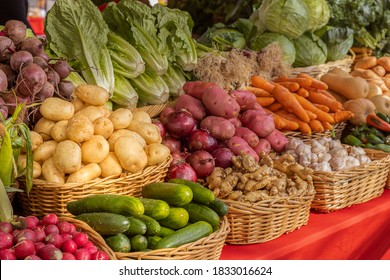 Organic fresh produce at the weekly farmers market downtown. A variety of locally grown yellow potatoes, red potatoes, ginger, cucumbers, carrots, butternut squash, lettuce, and greens on display.