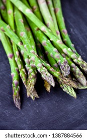 Organic fresh raw garden asparagus closeup on black board background. Green spring vegetables. Edible sprouts of asparagus. With copy space.