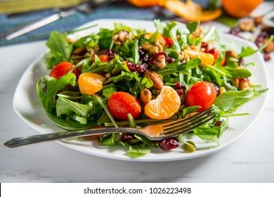 Organic fresh summer clementine salad with nuts and tomatoes