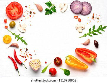 Organic fresh vegetables and spices frame on wooden white background. Copyspace, top view.