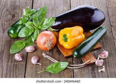 Organic fresh zucchini, eggplant, yellow capsicum, garlic and basil over rustic wooden background