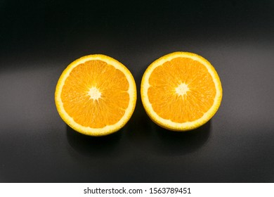Organic freshness Orange cutting on male hand Isolated pink background