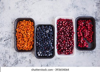 Organic frozen wild berries in plastic boxes packaging tray. Wholesome medicinal wild brier and sea buckthorn used for various treatment picked in autumn.