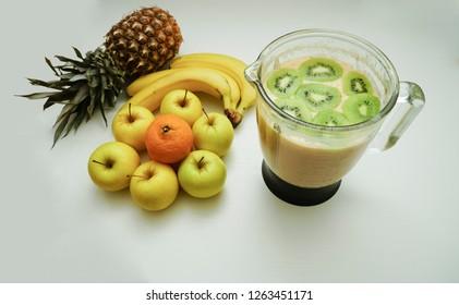 Organic fruit blending in juicer or blender on white table.