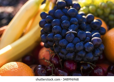 Organic fruit in summer grass. Fresh grapes, bananas and oranges in nature.