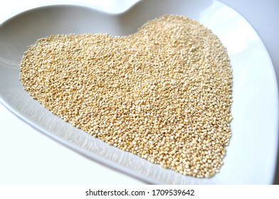 Organic gluten free quinoa grain in a heart shaped bowl on white with copy space