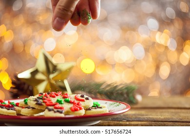 Organic Gluten Free Smiling Gingerbread Sugar Cookies On Holiday Plate And Wooden Background By Glowing Light Fireplace With Hand Dropping Sprinkles On Top.