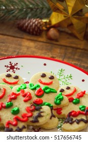 Organic Gluten Free Smiling Gingerbread Sugar Cookies On Holiday Plate And Wooden Vertical Background By Glowing Light Fireplace.