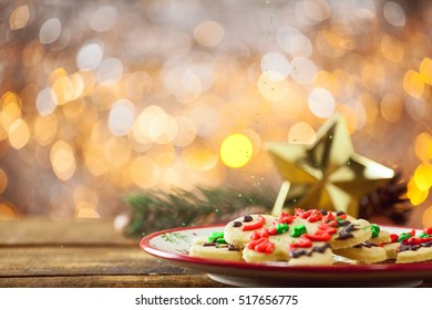 Organic Gluten Free Smiling Gingerbread Sugar Cookies On Holiday Plate And Wooden Background By Glowing Light Fireplace With Sprinkles Falling.