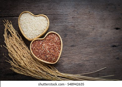 Organic grain brown rice in heart shape bamboo basket over wooden background