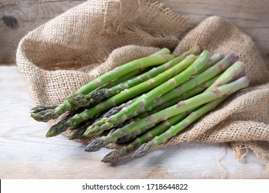 Organic green asparagus (Asparagus officinalis) fresh from the market on coarse burlap and rustic wood, copy space, selected focus, narrow depth of field