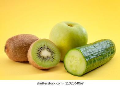 Organic green fruits and vegetables concept with close up on cucumber, apple and kiwi isolated on minimalist yellow background