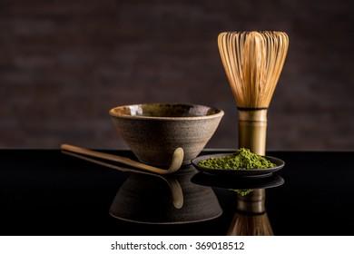 Organic green matcha tea in a bowl and matcha utelsils