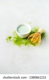 Organic green tea Matcha powder with Japanese tools Chasen bamboo whisk, bowl for brewing on concrete background with copy space.