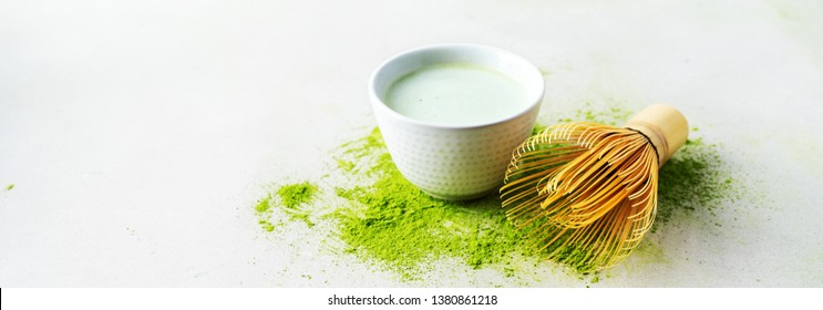 Organic green tea Matcha powder with Japanese tools Chasen bamboo whisk, bowl for brewing on concrete background. Long wide banner with copy space.