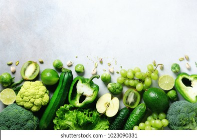 Organic green vegetables and fruits on grey background. Copy space, flat lay, top view. Green apple, lettuce, zucchini, cucumber, avocado, kale, lime, kiwi, grapes, banana, broccoli.