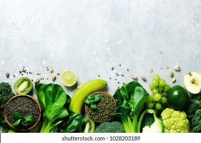 Organic green vegetables and fruits on grey background. Copy space, flat lay, top view. Green apple, zucchini, cucumber, avocado, kale, lime, kiwi, grapes, banana, broccoli, marbled lentils, mung bean