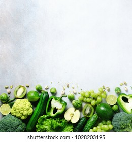Organic green vegetables and fruits on grey background. Copy space, flat lay, top view. Green apple, lettuce, zucchini, cucumber, avocado, kale, lime, kiwi, grapes, banana, broccoli