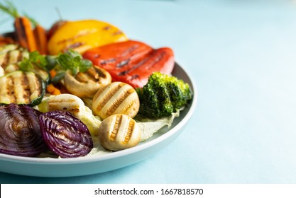 Organic grilled vegetables bell pepper, cauliflower,broccoli,carrots,mushrooms and red onions served on a round plate. Vegetarian dinner serving of roasted vegetables.