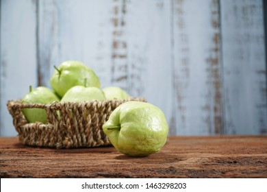 Organic guava on wooden table and wPosen background. Tropical fruits for good healthy ideas concept. Shoot in studio. Selective focus and free space for text.