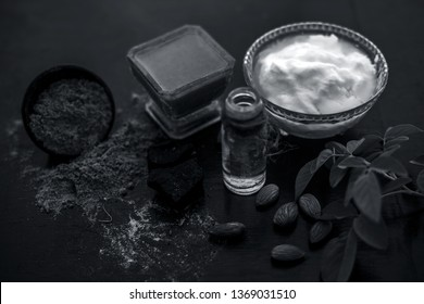 Organic hair conditioner on wooden surface i.e. Hing or devil's dung and almond oil with yogurt in a glass bowl and all the raw ingredients present on the surface with some rose leaves.