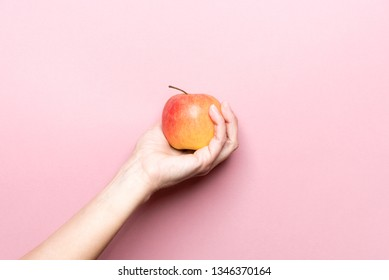 Organic healthy apple in a woman hand. Pink background.