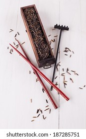 Organic healthy black wild rice in a wooden box with chopsticks and scattered rice grains  on a white wooden background