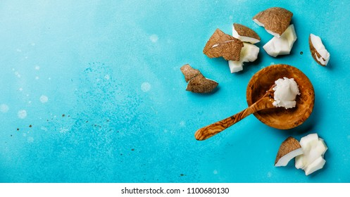 Organic healthy Coconut butter and fresh coconut pieces on blue background copy space