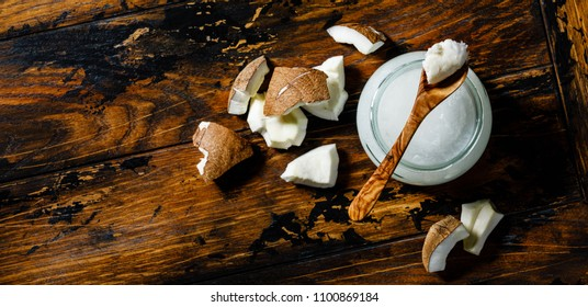 Organic healthy Coconut butter and fresh coconut pieces on wooden background copy space