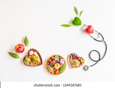 Organic  healthy  food,fruits,vegetable  in  wooden  bowls,stethoscope,red,green  heart  and  leaves  herb  on  white  background  for  creative  healthcare  and  ecology  concept