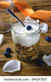 Organic and healthy granola parfait with blueberries and colorful rustic background. Country, casual, raw, simple, organic choices food styling.