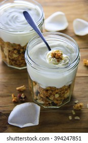 Organic and healthy granola parfait topped with yogurt on rustic wooden background. Country, casual, raw, simple, organic choices food styling.