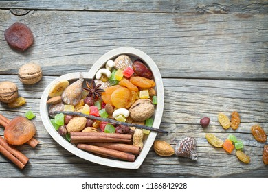 Organic healthy snacks dried fruits and nuts in heart food background