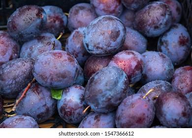 Organic healthy violet plum harvest  on the outside street market harvest day. Box full of fresh wet blue ripe plums, seasonal autumn tasty snack . Delicious raw vegetarian nutrition