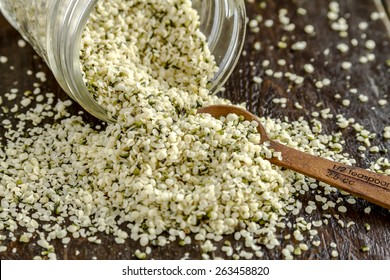 Organic hemp seeds spilling out of glass jar with measuring spoon on wooden table