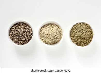 Organic hemp whole seeds, hulled seeds and protein powder in bowls on a white background