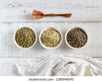 Organic hemp whole seeds, hulled seeds and protein powder in bowls on a white wooden background