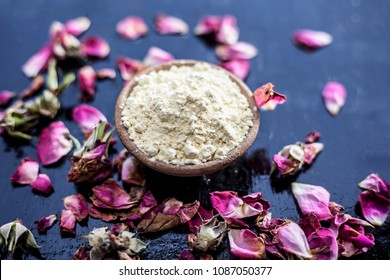 Organic and herbal face pack of Honey & Gram flour with its thick liquid mixture and some rose petals for good aroma on wooden surface used to cure acne & pimple by both males and females.