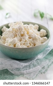 Organic homemade cottage cheese in a ceramic bowl on the kitchen table