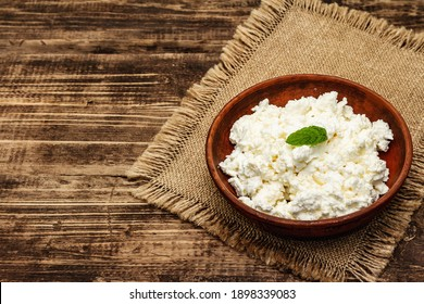 Organic homemade cottage cheese or curd in bowl on wooden rustic background, copy space