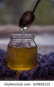 Organic honey in glass jar surrounded by spring blossom purple lilac.