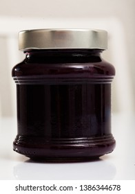 Organic huckleberry jam in glass jar on white table