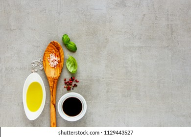 Organic ingredients and wooden spoon on light background flat lay. Top view, copy space. Healthy cooking concept.