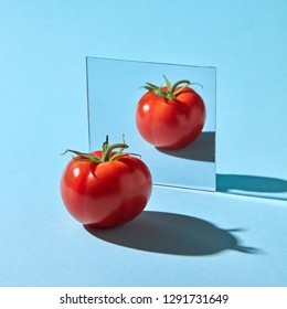 Organic juicy tomato with reflection in the mirror presented on a blue background with space for text. Healthy vegetable