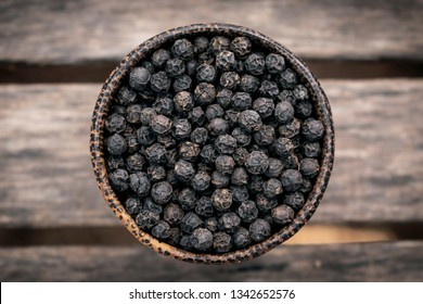 organic kampot dried black pepper corns in traditional wood bowl in cambodia