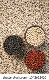 Organic kampot white red and black pepper corns in natural rustic style traditional wood bowls in cambodia on white peppercorn background